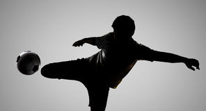 Ποδοσφαιριστής σκιαγραφιών που κλωτσά τη σφαίρα Στοκ φωτογραφίες με δικαίωμα ελεύθερης χρήσης
