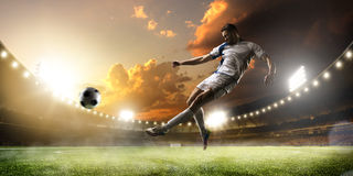 Ποδοσφαιριστής στη δράση στο υπόβαθρο πανοράματος σταδίων ηλιοβασιλέματος Στοκ Εικόνες