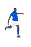 Ποδοσφαιριστής στο μπλε λάκτισμα Στοκ εικόνα με δικαίωμα ελεύθερης χρήσης
