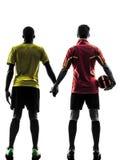 Ποδοσφαιριστής δύο ατόμων που στέκεται χέρι-χέρι τη σκιαγραφία Στοκ Εικόνα