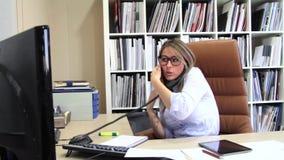 Πολυάσχολη επιχειρηματίας που μιλά με το κύτταρο και το σταθερό τηλέφωνο γραμμών στην αρχή απόθεμα βίντεο