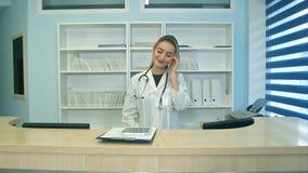 Πολυάσχολη νέα νοσοκόμα που χρησιμοποιεί την ταμπλέτα και το τηλέφωνο στο γραφείο υποδοχής Στοκ φωτογραφίες με δικαίωμα ελεύθερης χρήσης