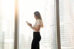 Πολυάσχολη σοβαρή επιχειρηματίας που χρησιμοποιεί την ψηφιακή ταμπλέτα, που στέκεται κοντά στο β Στοκ φωτογραφίες με δικαίωμα ελεύθερης χρήσης