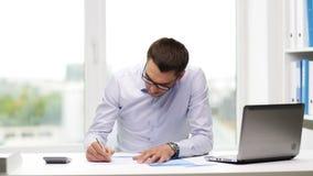 Πολυάσχολος επιχειρηματίας με το lap-top και έγγραφα στην αρχή απόθεμα βίντεο