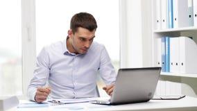 Πολυάσχολος επιχειρηματίας με το lap-top και έγγραφα στην αρχή φιλμ μικρού μήκους