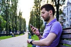 Πολυάσχολος νεαρός άνδρας με το ρολόι που εξετάζει το τηλέφωνο υπαίθρια Στοκ φωτογραφία με δικαίωμα ελεύθερης χρήσης