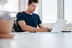Πολυάσχολος νεαρός άνδρας που εργάζεται στο φορητό προσωπικό υπολογιστή στην αρχή Στοκ εικόνες με δικαίωμα ελεύθερης χρήσης