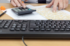 Πολυάσχολος υπολογισμός οικονομικού απολογισμού στο γραφείο του Στοκ εικόνες με δικαίωμα ελεύθερης χρήσης