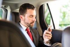 Πολυάσχολο άτομο σε ένα κοστούμι που χρησιμοποιεί το smartphone του Στοκ Εικόνες