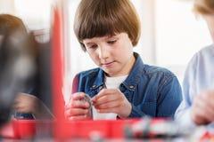 Πολυάσχολο σοβαρό αγόρι που κρατά τη λεπτομέρεια ρομπότ Στοκ φωτογραφίες με δικαίωμα ελεύθερης χρήσης