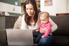 Πολυάσχολο mom που λειτουργεί στο σπίτι Στοκ Εικόνες