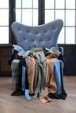 Πολυθρόνα με τα ενδύματα, φορέματα στις κρεμάστρες στοκ φωτογραφία με δικαίωμα ελεύθερης χρήσης