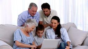 Πολυμελής οικογένεια που χρησιμοποιεί το lap-top από κοινού απόθεμα βίντεο