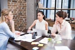 Πολυπολιτισμικές επιχειρηματίες που συζητούν το επιχειρησιακό πρόγραμμα στον εργασιακό χώρο με το lap-top Στοκ Εικόνα