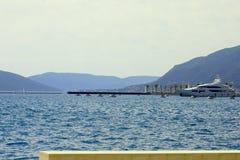 Πολυτελής βάρκα που δένεται σε έναν όμορφο κόλπο που περιβάλλεται από το mounta στοκ φωτογραφία
