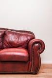 Πολυτελής κόκκινος καναπές δέρματος μπροστά από έναν κενό τοίχο Στοκ Φωτογραφίες