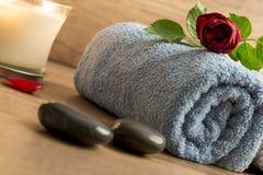 Πολυτελής ρύθμιση wellness με μια κυλημένη μπλε πετσέτα, κόκκινα ros Στοκ Εικόνες