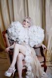 Πολυτελής συνεδρίαση γυναικών στην καρέκλα, κορίτσι στο άσπρο μακρύ φόρεμα Το ανυψωτικό πόδι, γοητεία εξετάζει τη κάμερα, σκοτάδι Στοκ Φωτογραφία