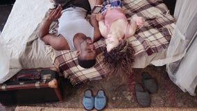 Πολυφυλετικό ζεύγος που βρίσκεται στο κρεβάτι, μουσική ακούσματος στο smartphone Άνδρας και γυναίκα στις πυτζάμες που περνούν το  Στοκ εικόνες με δικαίωμα ελεύθερης χρήσης
