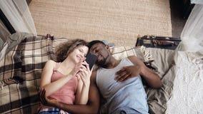 Πολυφυλετικό ζεύγος που βρίσκεται στο κρεβάτι Ο άνδρας και η γυναίκα ξοδεύουν το χρόνο μαζί με τη χαρά και ο θαυμαστής, χρήση Sma Στοκ Φωτογραφία