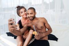 Πολυφυλετικό ζεύγος που κάνει selfie και που κρατά τα κοκτέιλ στην παραλία Στοκ Φωτογραφία