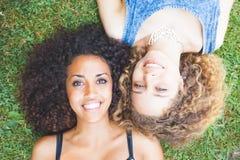 Πολυφυλετικό θηλυκό ζεύγος των φίλων που βρίσκονται στη χλόη Στοκ Φωτογραφία
