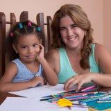 Πολυφυλετικό μικρό κορίτσι και το σχέδιο μητέρων της με τα μολύβια χρώματος Στοκ εικόνα με δικαίωμα ελεύθερης χρήσης