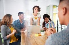 Πολυ εθνική ομάδα επιτυχών δημιουργικών επιχειρηματιών που χρησιμοποιούν ένα lap-top κατά τη διάρκεια της ειλικρινούς συνεδρίασης Στοκ Εικόνες
