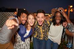 Πολυ-εθνική millenial ομάδα φίλων που παίρνουν μια φωτογραφία λάμψης selfie με το κινητό τηλέφωνο στη στέγη terrasse στη νύχτα Στοκ Εικόνα