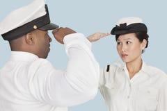Πολυ-εθνικοί ανώτεροι υπάλληλοι Αμερικανικού Ναυτικό που χαιρετίζουν ο ένας τον άλλον πέρα από το ανοικτό μπλε υπόβαθρο στοκ εικόνα