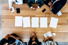 Πολυ-εθνικοί επιχειρηματίες στη συνεδρίαση με τις κενές σελίδες στο tabl Στοκ Εικόνες