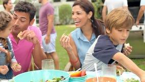 Πολυ οικογένεια παραγωγής που απολαμβάνει το γεύμα στον κήπο από κοινού απόθεμα βίντεο