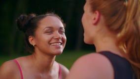 Πολυ φυλετικές φίλες που μιλούν στο θερινό πάρκο Κινηματογράφηση σε πρώτο πλάνο των πολυ εθνικών κοριτσιών απόθεμα βίντεο