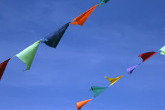 Πολυ χρωματισμένες μικρές τριγωνικές δίκαιες σημαίες σε ένα σχοινί σε ένα μπλε SK Στοκ Φωτογραφίες