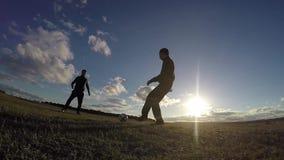 ποδόσφαιρο Δύο άτομα σκιαγραφούν το παίζοντας ηλιοβασίλεμα ποδοσφαίρου ποδοσφαίρου τρόπου ζωής ο αθλητισμός απόθεμα βίντεο