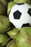 Ποδόσφαιρο σφαιρών ποδοσφαίρου που στηρίζεται με τις φρέσκες πράσινες καρύδες Στοκ Εικόνες