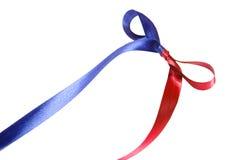 Πολύχρωμα μπλε-κόκκινα κορδέλλα και τόξο υφάσματος στο άσπρο υπόβαθρο στοκ εικόνα με δικαίωμα ελεύθερης χρήσης