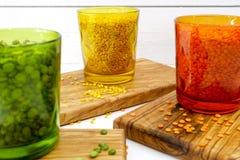 Πολύχρωμα σαφή γυαλιά με τα διάφορα όσπρια (πράσινα μπιζέλια, σχετικά με Στοκ Εικόνα