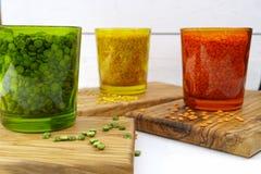 Πολύχρωμα σαφή γυαλιά με τα διάφορα όσπρια (πράσινα μπιζέλια, σχετικά με Στοκ Φωτογραφία