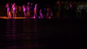 Πολύχρωμα φω'τα που γυρίζουν στη λέσχη νύχτας όταν χορεύουν οι άνθρωποι θολωμένος απόθεμα βίντεο
