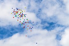 Πολύχρωμα Ballons που επιπλέουν σε έναν νεφελώδη μπλε ουρανό Στοκ Εικόνες