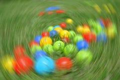 Πολύχρωμες σφαίρες - παιχνίδια των παιδιών, στην πράσινη χλόη, με την ακτινωτή θαμπάδα Στοκ Εικόνες