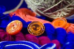 Πολύχρωμη γκρίζα σφαίρα νημάτων και πορτοκαλιά κουμπιά Στοκ Φωτογραφία