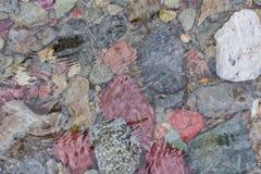 Πολύχρωμοι βράχοι κάτω από τους κυματισμούς του κολπίσκου Στοκ Εικόνα