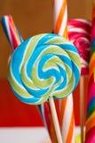 Πολύχρωμοι γλυκοί κάλαμοι και twirls καραμελών στα ξύλινα ραβδιά Στοκ Φωτογραφίες