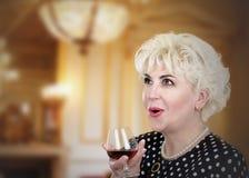 Πολύ έκπληκτη ώριμη γυναίκα με το ποτήρι του κονιάκ στοκ εικόνα