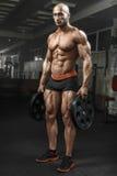 Πολύ αθλητικός τύπος δύναμης που στέκεται στη γυμναστική και που στη κάμερα Στοκ εικόνα με δικαίωμα ελεύθερης χρήσης
