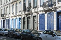 Πολύ γαλλικό κτήριο με τα μπλε παραθυρόφυλλα και τη σειρά των αυτοκινήτων Στοκ Εικόνα