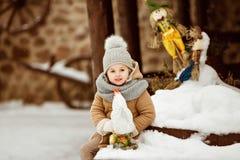 Πολύ γλυκό και αστείο παιδί κοριτσιών σε ένα μπεζ παλτό και ένα γκρίζο καπέλο s Στοκ Εικόνες