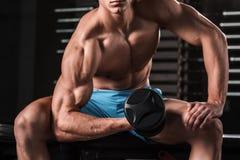 Πολύ ο αθλητικός τύπος δύναμης bodybuilder εκτελεί την άσκηση με τους αλτήρες στη σκοτεινή γυμναστική Στοκ φωτογραφία με δικαίωμα ελεύθερης χρήσης